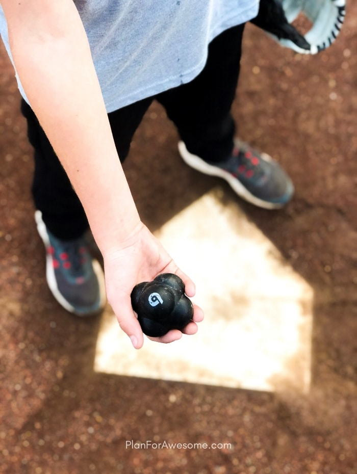 This boy is holding a reaction ball, that came in his baseball subscription box.  This thing is THE BEST GIFT EVER for baseball lovers...seriously the coolest and the easiest gift idea for baseball lovers and players!  A surprise box full of baseball gear, apparel, training aids, accessories, and snacks - I just ordered one for my little guy!  #baseballgiftideas #baseballmom